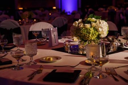 A close-up image of a round table set for a wedding reception labeled Table 1 with white linens and a green and white floral arrangement set in the center of the table while the rest of the tables in the background are out of focus set against a blue lit wall.