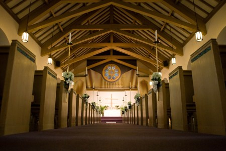 A ground floor view looking down the main aisle towards the altar of The Memorial Chapel in Akron, Ohio with the outside pews decorated with white and green flowers and the stunning wooden beams in the ceiling.