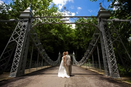An image of a bride and groom standing in the middle of a bridge back to back but holding hands with their faces turned cheek to cheek looking at the camera surrounded by the wrought iron pillars and rails of the bridge with green trees in the background under a blue sky.