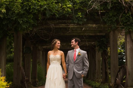 A bride in a strapless cream colored lace and tulle wedding gown is holding hands and turning her head to look at her groom in his grey tuxedo and bright pink tie while they stand under a wooden arbor with dark green foliage at Parker Ranch.