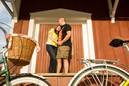 A picture of an engaged couple wearing yellow and black standing in front of a cute little red building trimmed in white white an old-fashioned bicycle in the foreground.