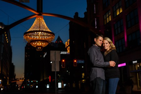 A picture of an engaged couple leaning into an embrace with their foreheads touching standing outside on the streets in Cleveland in jeans and dark shirts in the foreground of the left side while the stunning dark blue dusk sky sets in the background with the city lights on buildings and the Playhouse Square outdoor chandelier hangs with golden lights in the upper left corner of the background.