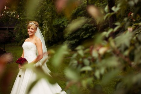 An outdoor image of a bride in a strapless white wedding gown holding a red bouquet of roses with a veil and crown on surrounded by lush green foliage at Roses Run Country Club in Stow, Ohio.