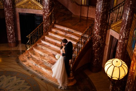 A photo of a bride leaning back onto her groom's arms while he is kissing her cheek and leaning on the gold and wrought iron railing on the far right side of the marble steps in the Grand Foyer of Severance Hall full of marble pillars and flooring.