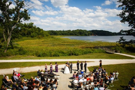 A bird's eye view of an outdoor wedding ceremony on a bright sunny day where the bride and groom are holding hands while the wedding party stands in attendance on a cement pad just below a v-shaped gravel path leading to a wooden bride and the blue Sippo Lake with green foliage in the background and wedding guests sitting in folding chairs watching.