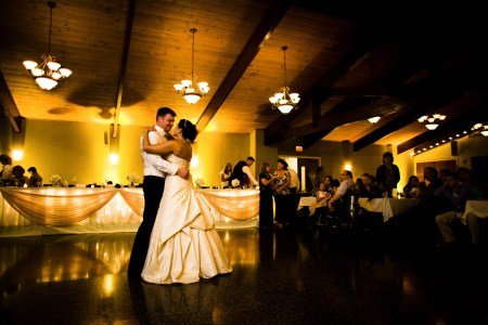 An image of a bride and groom slow dancing on the dark floor of the Skyland Pines reception hall with a wooden plank and beam ceiling lit up with golden yellow lights and the head table in the background with twinkle lights and tulle.