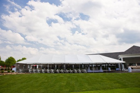 A picture taken of the outside of the Squaw Creek Country Club from the front green lawn with a large white tent in the very middle of the photo with white folding chairs lined up facing the right of the photo towards a square draped wedding altar all under a white puffy cloud sky.