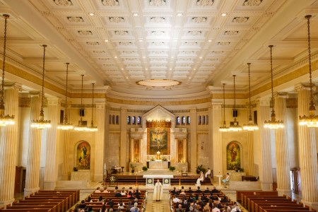 A photo taken from the balcony of St. Ann Church overlooking the large vaulted sanctuary that has cream colored walls and pillars with ornate paintings set in marble on the back wall of the altar and where the priest is standing in the center aisle while the wedding guests are seated in the pews and the bride and groom are seated to the right of the altar area.