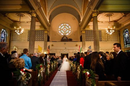 An image of a bride walking down the center aisle from the back of the church holding hands with her mom as they walk over a white aisle runner overtop of dark red carpeting, with the cream colored back wall of the sanctuary behind them with a large round stained glass window at the top center of the photo and the guests on either side standing and watching from the pews decorated with red and white roses bunched with greenery and gold bows at St. Elizabeth of Hungary.