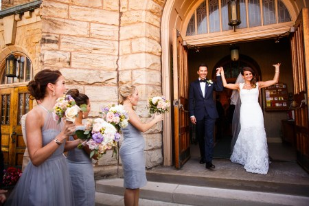 A bride and groom holding hands up high with smiles exiting St. Vincent church with double wooden door and stone walls with the bridesmaids in grey blue dresses holding purple and pink bouquets cheering them on.