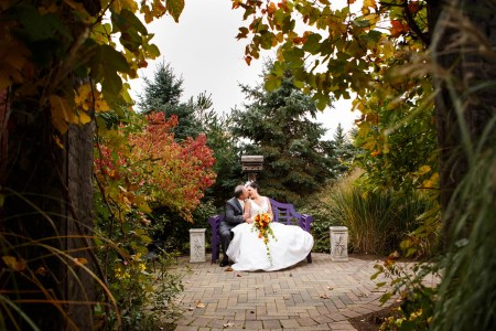 A bride holding a bright fall colored bouquet leaning into her groom for a kiss while they are sitting on a purple bench set on a round brick patio in the middle of a garden with fall foliage at the Thorncreek Winery.