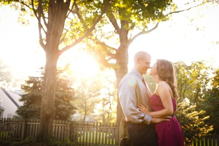An image of an engaged couple standing nose to nose with their hands on each other's waists where the woman has on a fuchsia strapless dress and the man is wear a grey button down shirt with matching tie while standing outside in a residential backyard with a brown picket fence in the background with green trees and shrubs while the bright sun shines down on the couple creating a beautiful sunny haze.