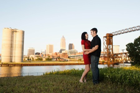 An engaged couple stand on a patch of grass in the right of the photo looking into each other's eyes with their hands on each other's waists where the woman is wearing a short red dress and the man is wearing a black golf shirt and jeans with the river and the Cleveland skyline is in the background on a sunny evening.