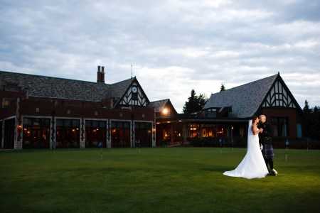 A picture taken of a bride in her long white gown with a long veil standing with her groom dressed in kilt in the far right of the photo on the green front lawn of the Tudor and red brick style building of the Youngstown Country Club taken at dusk with a golden light shining from the building all under a grey cloudy sky.