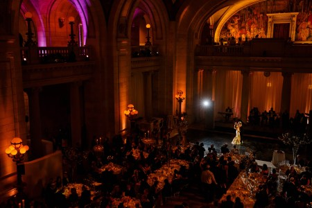 A bird's eye view of a bride and groom dancing at their reception inside the darkened ballroom of the Old Courthouse set with golden orange up lights, marble pillars, and vaulted ceilings and the guests are all seated.