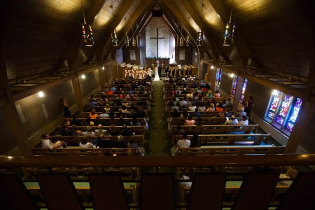 A bird's eye view of a wedding ceremony taken from the balcony of Greensburg United Methodist Church looking down the center aisle carpeted in olive carpet with white flower petals dropped and wooden pews on either side filled with guests watching the bride and groom standing with the pastor and the wedding party in front of the altar with a white stone wall and a large wooden cross all inside a sanctuary of wooden and brick walls with stained glass windows on the right.