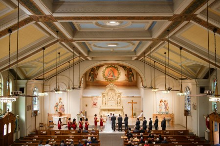 A photo taken from the balcony of the Holy Rosary Church overlooking a bride and groom facing the altar with the bridesmaids on the right in red dresses and the groomsmen on the left in black tuxedos in the bright sanctuary with the walls and square ceiling patterns in yellow and blue.