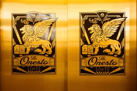An image of the closed golden double elevator doors at The Onesto Lofts with a black and gold image of their winged lion logo and name on both doors.