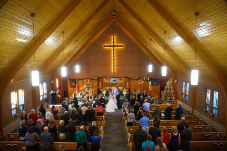 A photo of a wedding ceremony where the bride and groom are standing in the center of the photo at the end of the center aisle facing each other and holding hands while the guests stand up from the wooden pews under a tall triangular ceiling made of wooden planks and curved wooden beams with a brick wall behind the altar with a large wooden cross lit with yellow lights from behind.