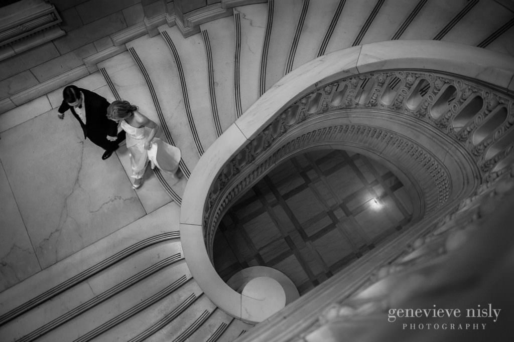 Bride and groom walk down grand staircase at the old courthouse.