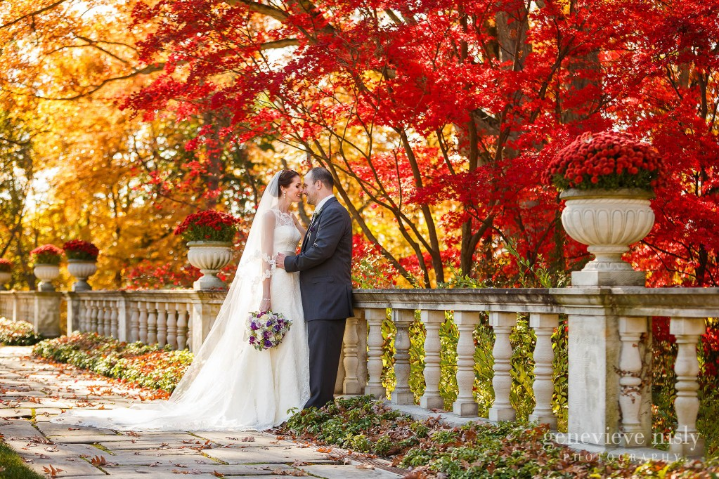 Akron wedding couple at Stan Hywet Hall and Gardens in front of red and yellow fall colors.