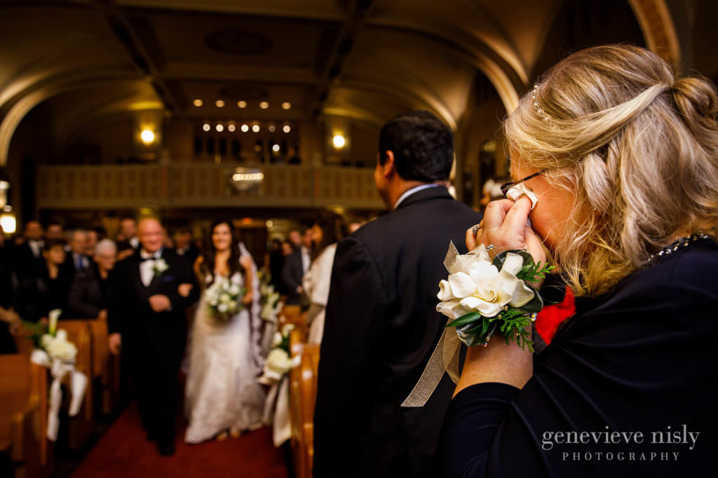Mom wipes a tear as the bride walks down he aisle with her dad.