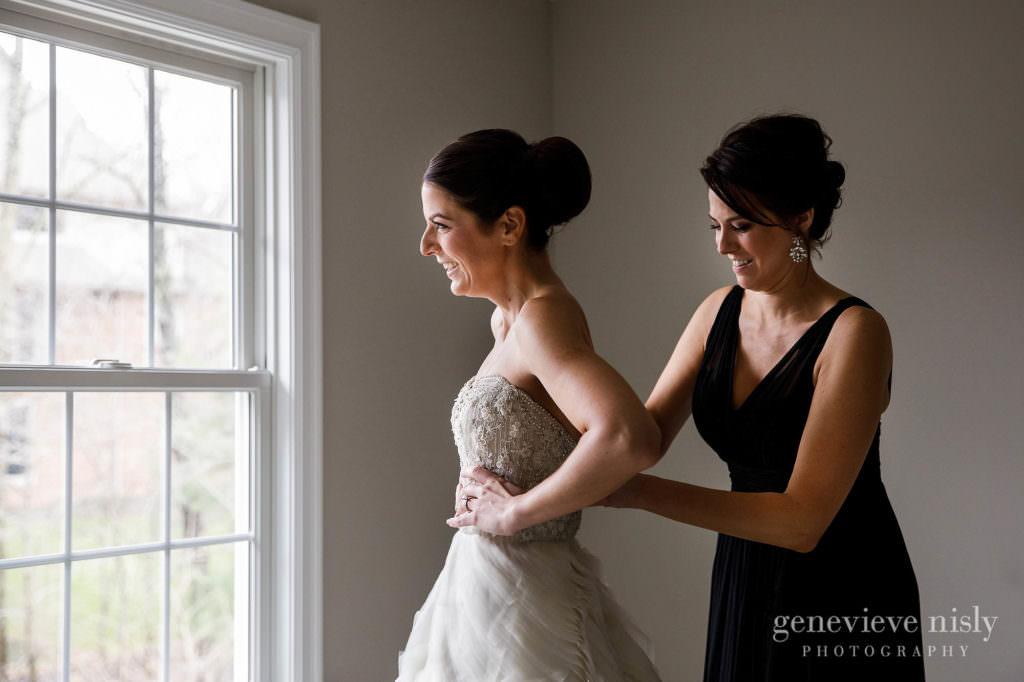 Maid of honor helps the bride zip up her wedding dress.