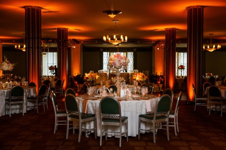 An image of a room at The Silver Grille decorated for a wedding reception where a round table with green and silver chairs are at the focal point in the center of the photo white tablecloth and pink linens and a pink and white floral arrangement is set on a tall silver holder and the background of the photo shows four pillars light up with orange glowing lights that shine up towards the ceiling.