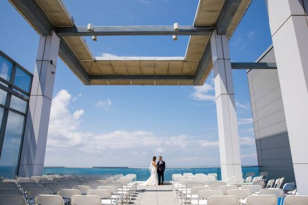 An image of a bride in her white dress standing with her groom against the glass railing on a sunny summer day with blue skies and puffy clouds and a view of Lake Erie behind them from the balcony set with white folding chairs lined up for the ceremony at the Aloft building in downtown Cleveland, OH.