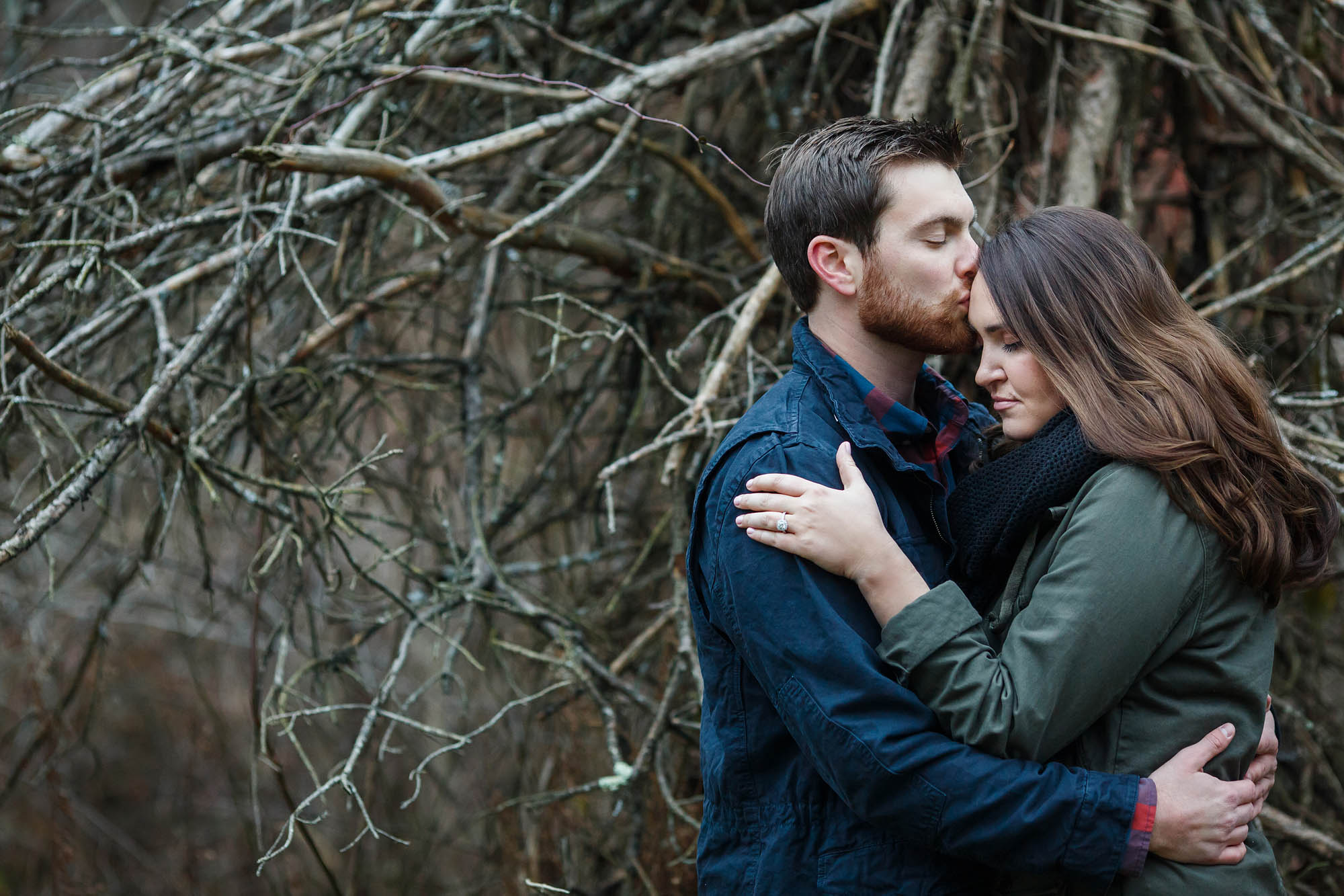 Man kisses women's forehead during a winter engagement photo session.