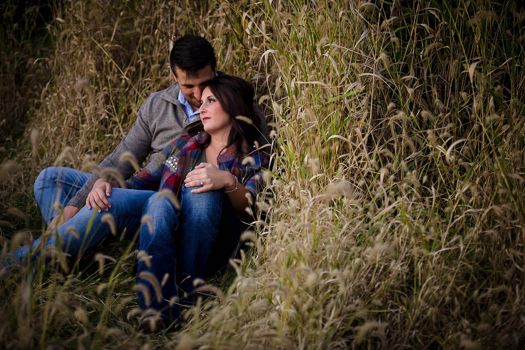An engaged couple wearing jeans sits back in each other's arms while they lean into tall grassy like weeds during autumn in New Philadelphia, Ohio.