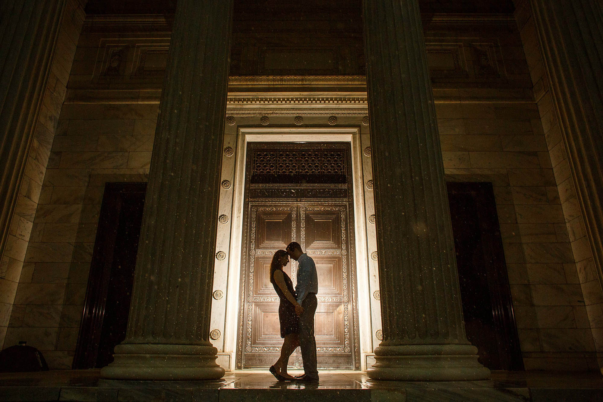 An engaged couple stand with their foreheads together in the doorway of the Cleveland Art Museum at night where the doorframe is light up and the couple is silhouetted against it.