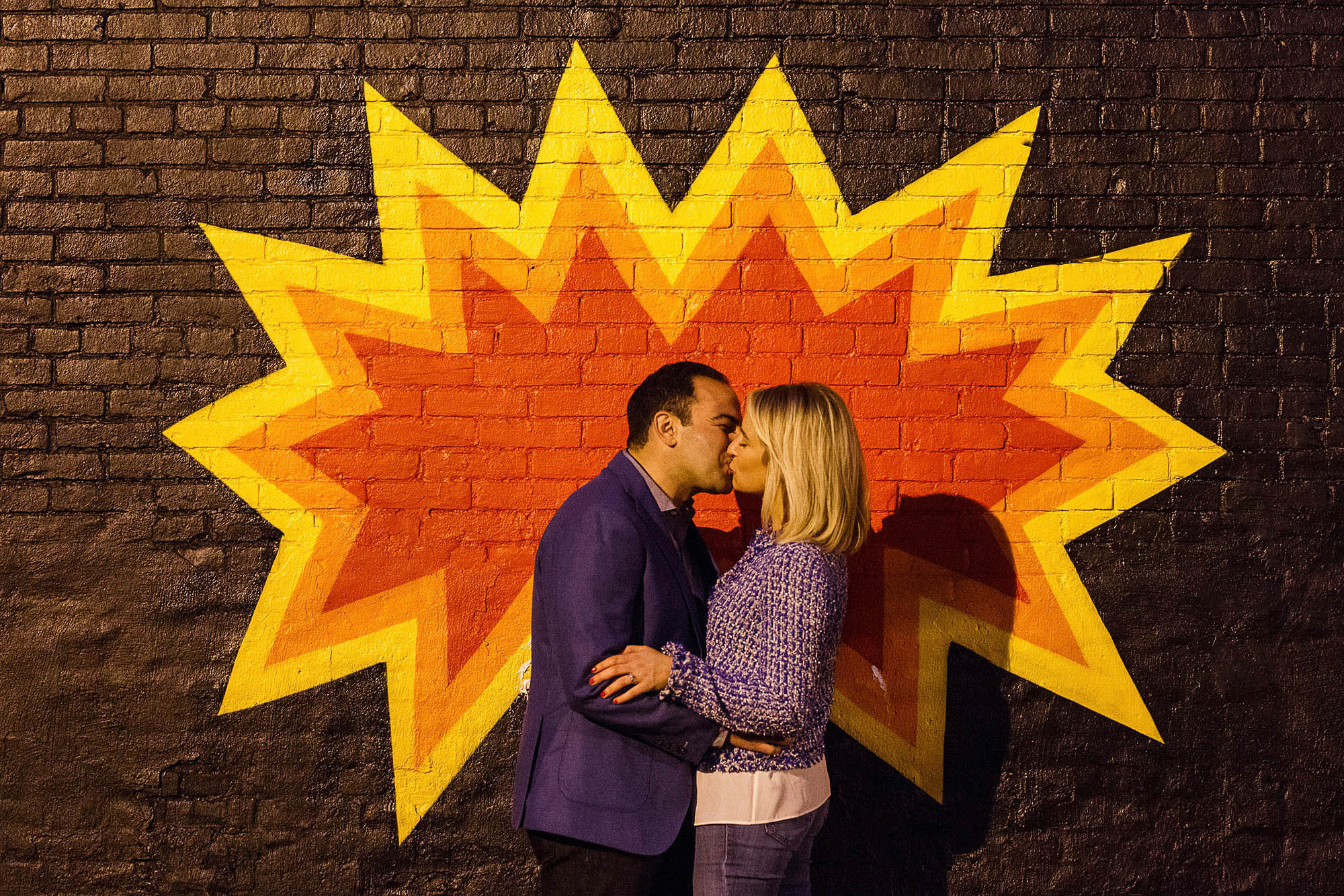 A picture taken from waist high of an engaged couple holding each other and kissing outside against a brown brick building with a a zig zag burst pattern in red, orange, and yellow painted on the wall directly behind them taken in a city in Ohio.