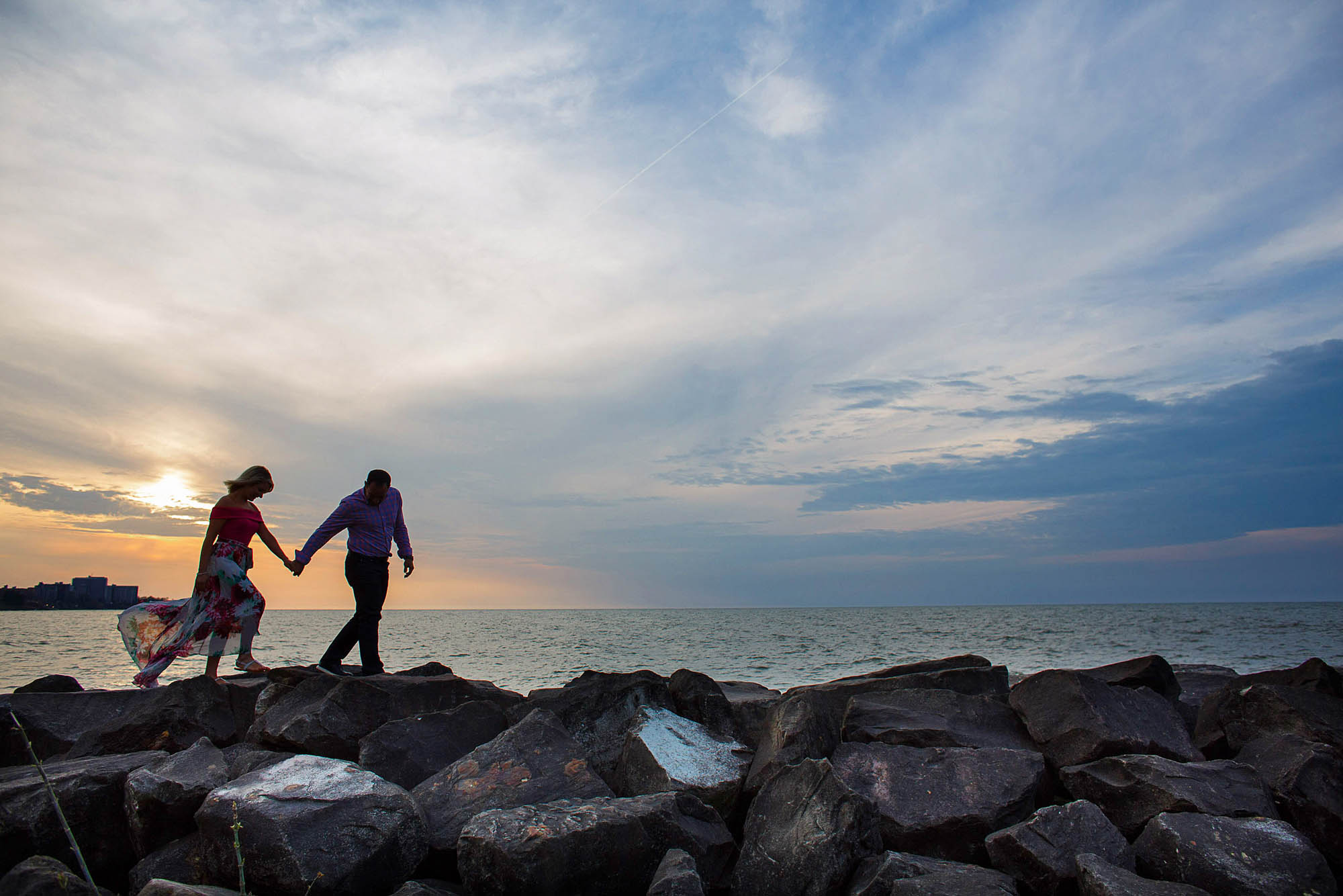 A picture taken at sunset on a cloudy evening of an engaged couple walking hand in hand in the lower left of the photo along a large stone path at Edgewater Park in Ohio with Lake Erie in the background.