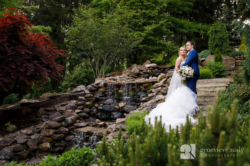 Bride and groom embrace on the side of a hill during their backyard wedding.