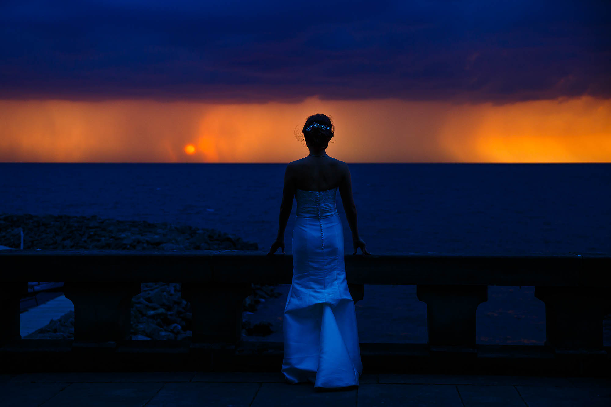 A bride watches the storm roll in over Lake Erie at the Shoreby Club in Cleveland, Ohio during the wedding reception.