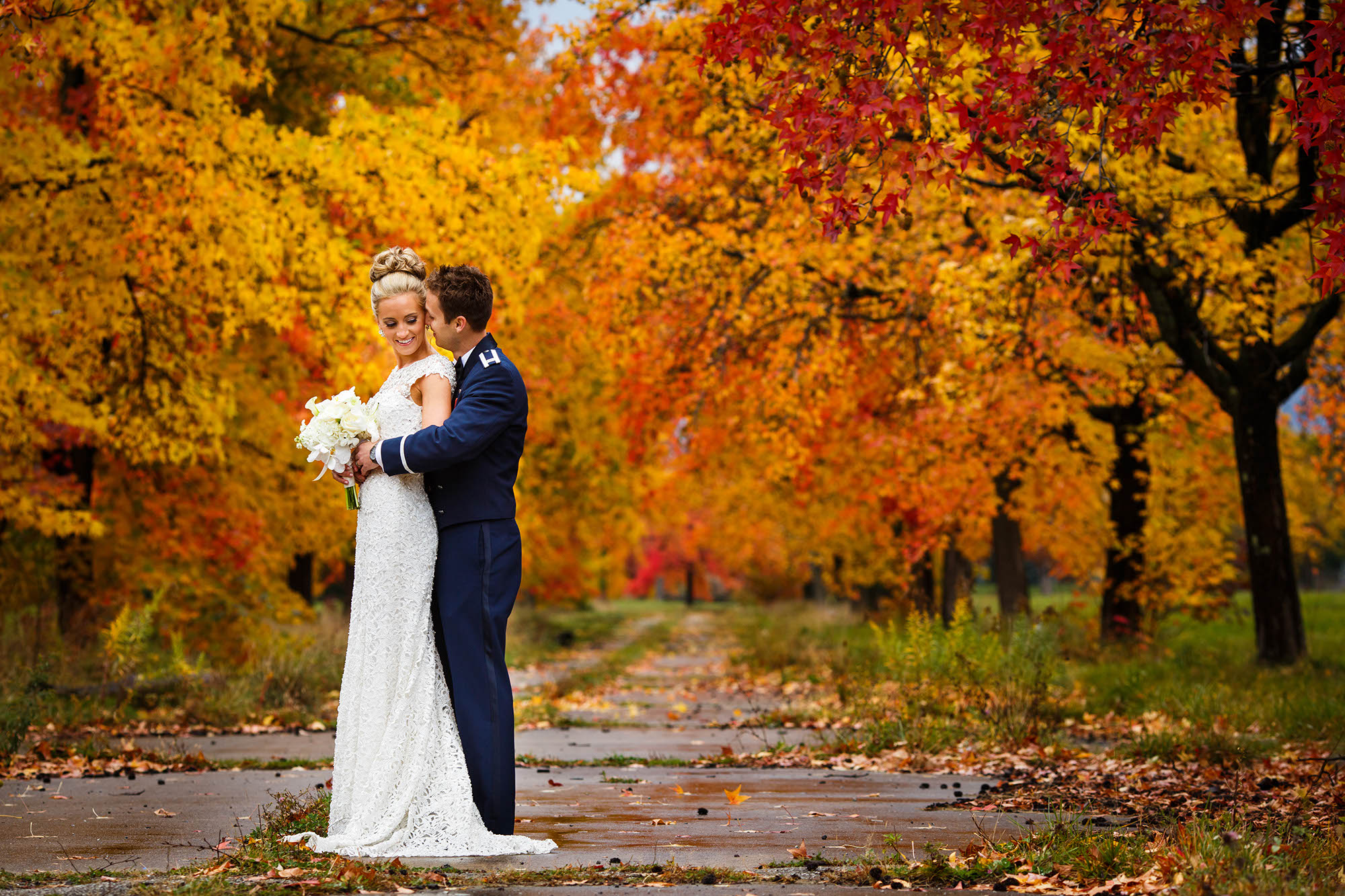 A vibrant photo taken of a bride and groom during the height of the fall foliage with bright red, orange, and yellow leaves in the background while standing on an abandoned driveway near the Cleveland Hopkins Airport in Cleveland, Ohio.