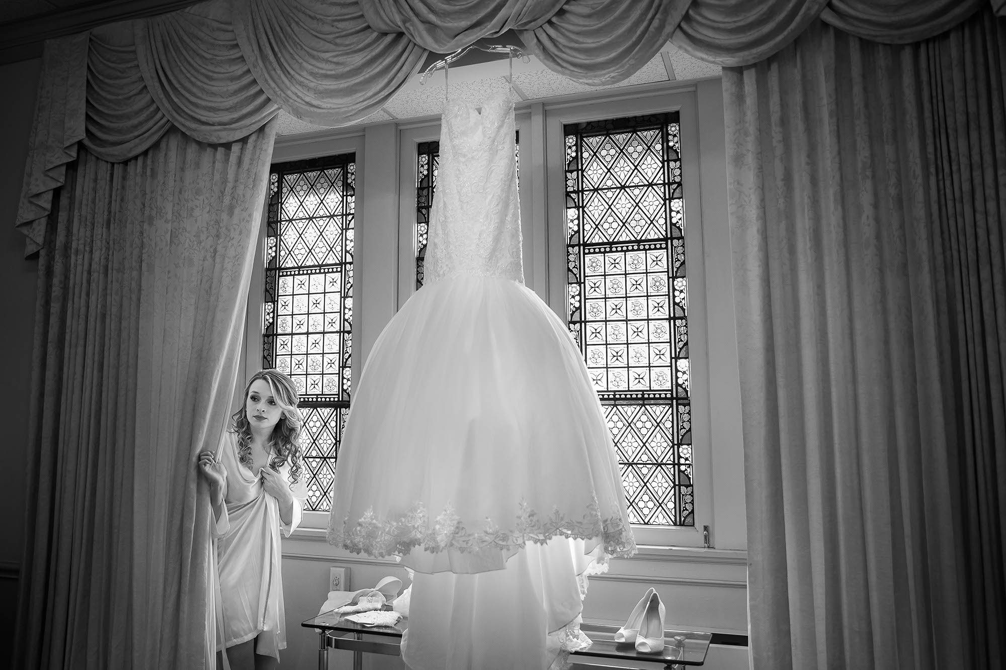 The candid moment of the bride peaking around the curtains of the stained glass window at Crossroads United Methodist Church in downtown Canton, Ohio.