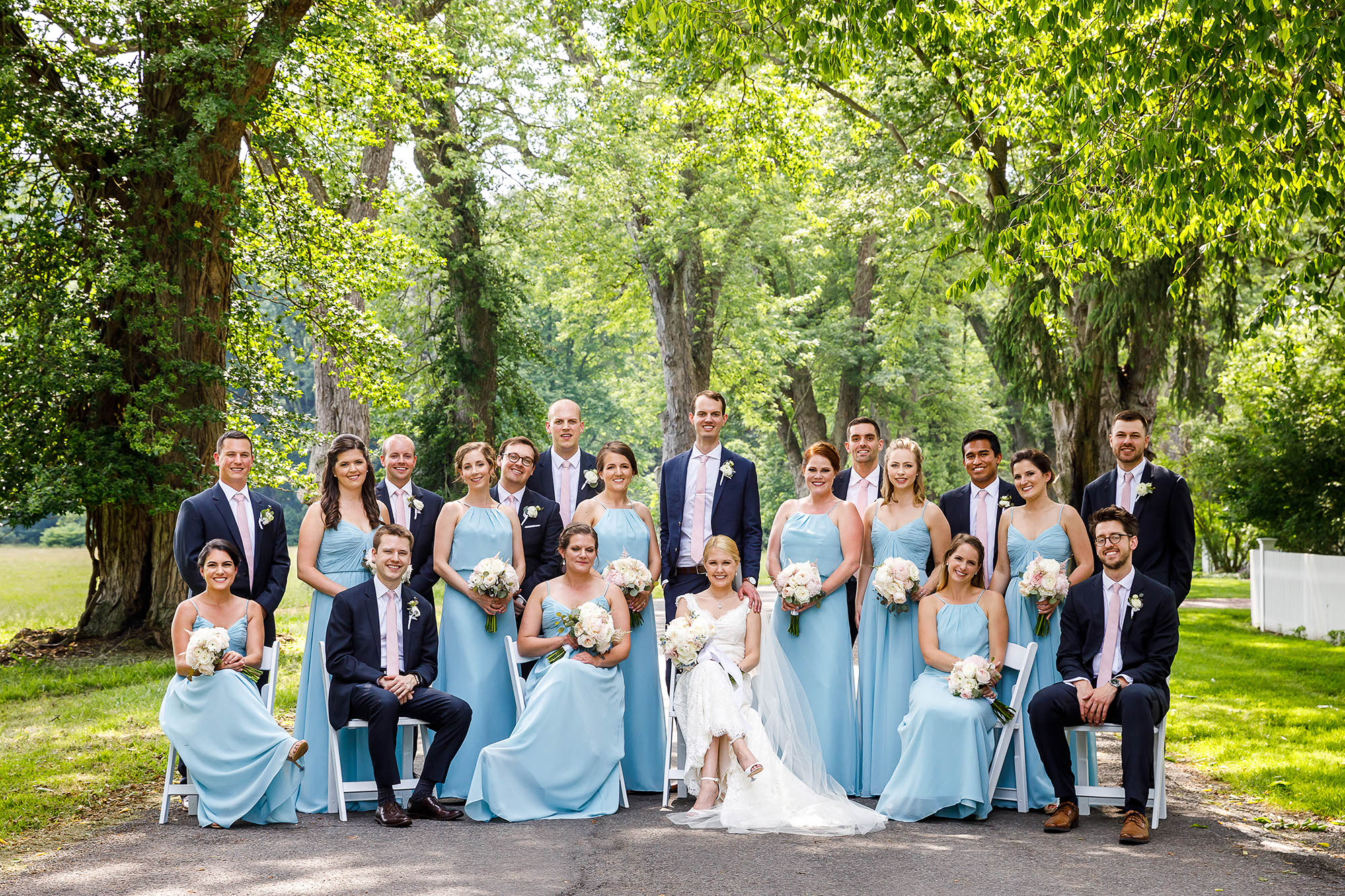 A wedding party sports their light blue gowns and dark blue tuxedos outside on a beautiful, sunny day. Tall oak trees and green grass surround them at The Hunt Club in Gates Mills, Ohio.