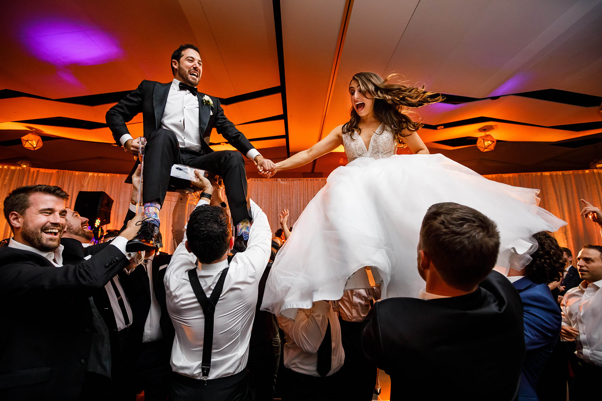 A Jewish bride and groom both lifted up on chairs laughing during the horah dance at the wedding at the Hilton Cleveland Downtown in Cleveland, Ohio.