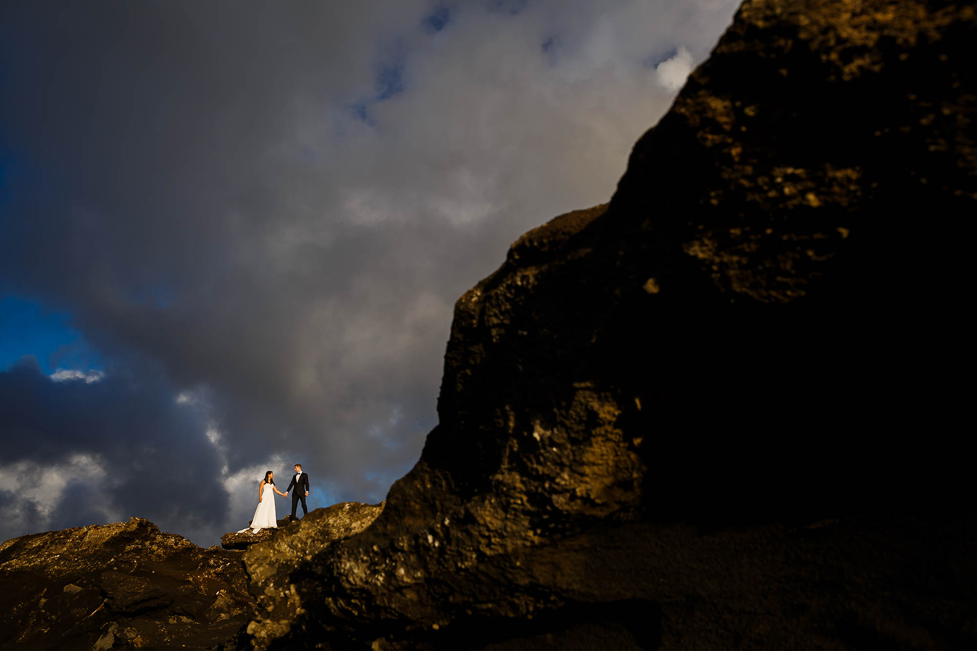 A wedding couple standing hand and hand on the rocky cliffs of Southern Iceland while the sun shines down on them and huge grey puffy clouds gather in the background.