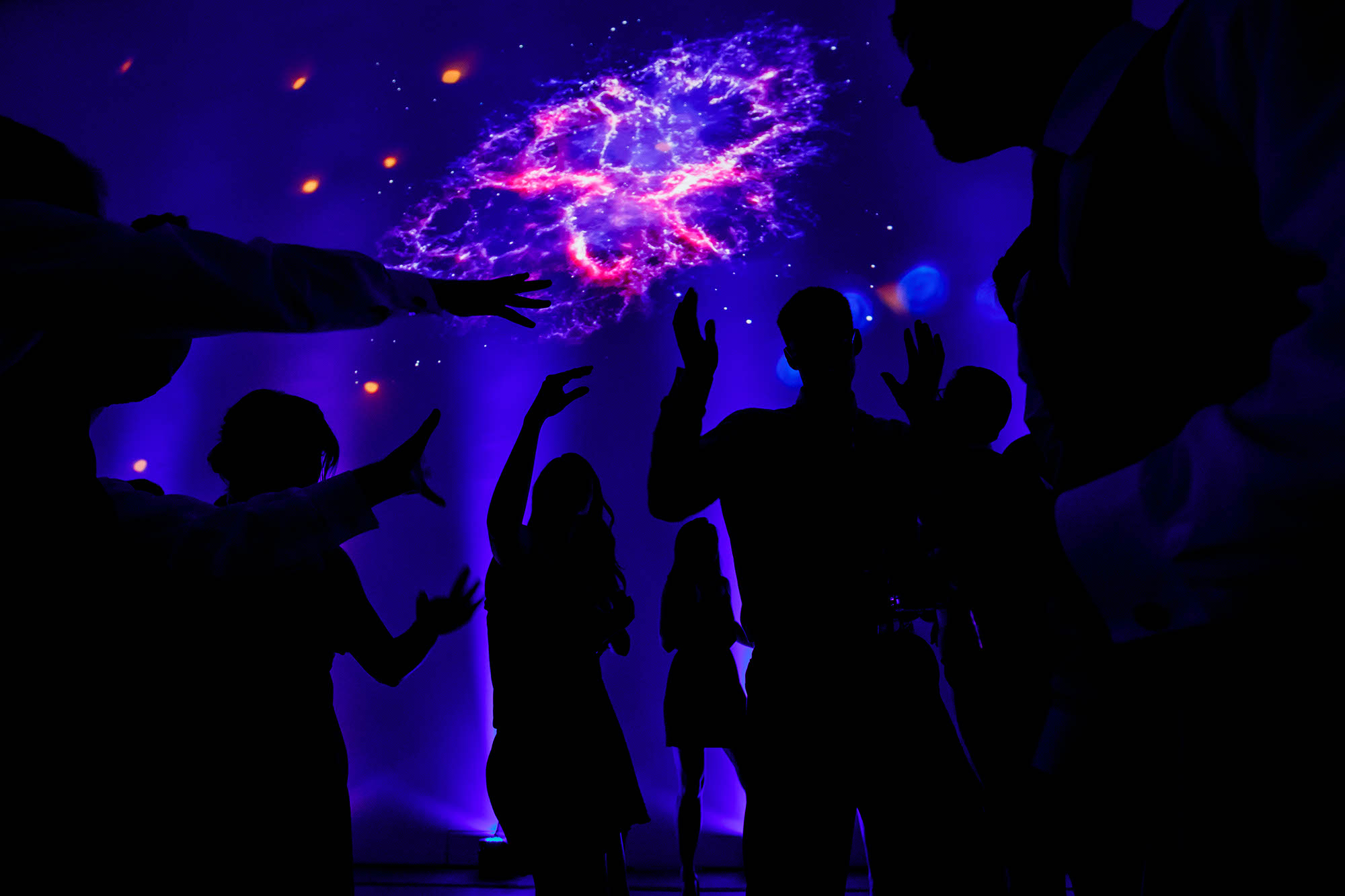 Reception guests dance the night away under a projected image of galaxies and stars at the Museum of Contemporary Art located in downtown Cleveland, Ohio.