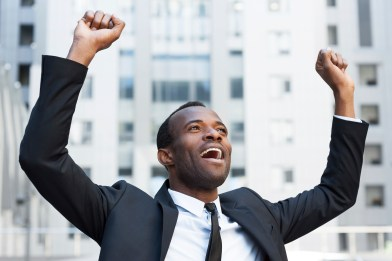 Business winner. Happy young African man in formalwear keeping arms raised and expressing positivity while standing outdoors
