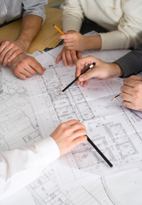 Commercial electricians reviewing location blue prints for building