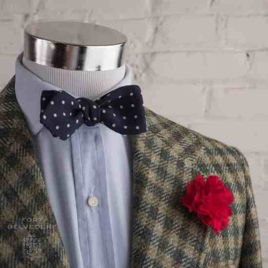 Tweed sport coat with dark red carnation boutonniere with wool challis polka dot paisley bow tie with pointed ends by Fort Belvedere
