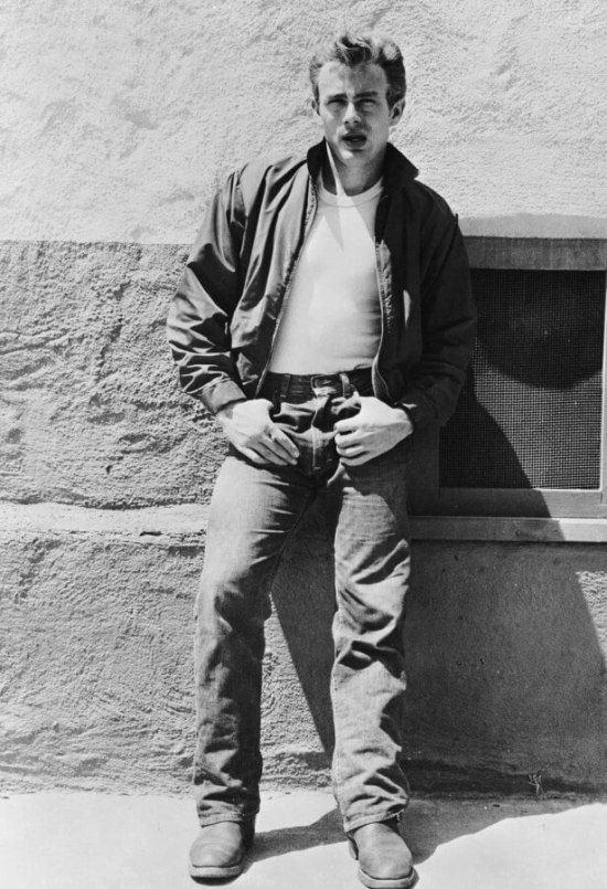 James Dean in Rebel Without a Cause, sporting his iconic ensemble of red Harrington jacket, white T-shirt, jeans, and boots.