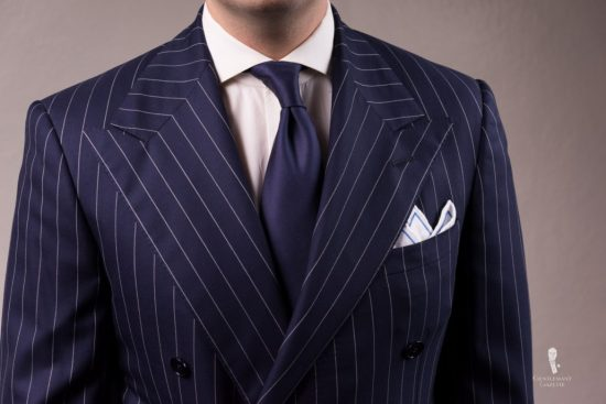 Chalk stripe suit with navy tie and White Irish Linen Embroidered Contrast Framing Pocket square