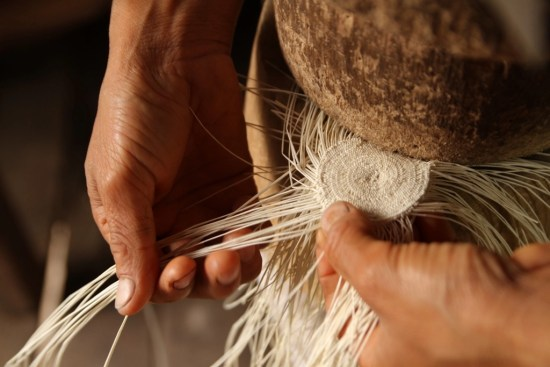 Hand weaving the crown of a Panama hat