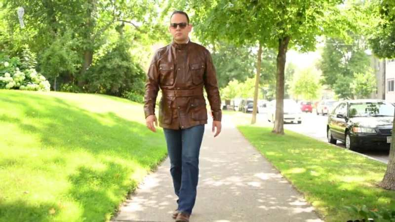Raphael walking outdoors while wearing a brown Trialmaster Panther, denim jeans, brown boots, and sunglasses