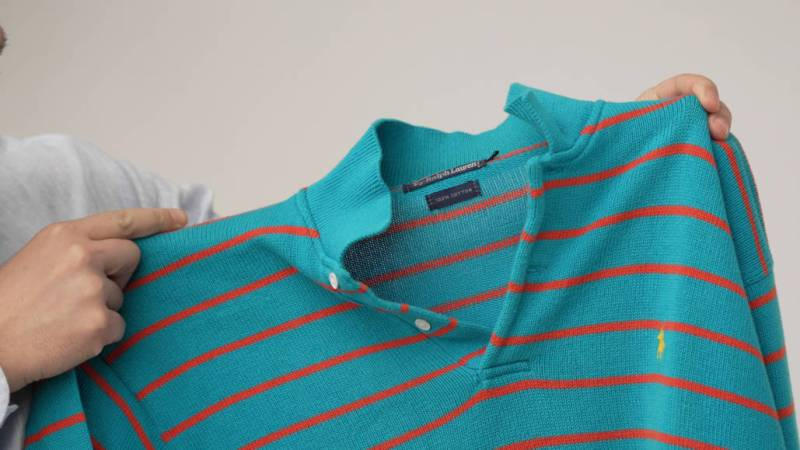 Raphael holding a turquoise knitted polo shirt with orange stripes